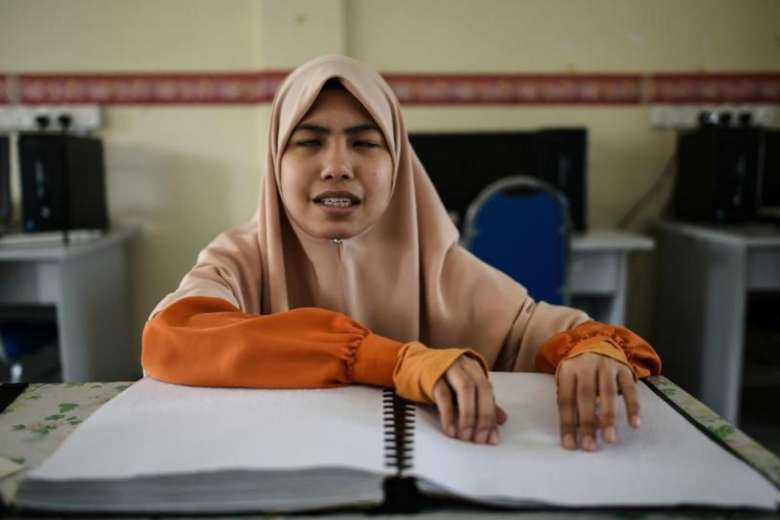 Cara OKU Penglihatan sedang membaca Al Quran Braille